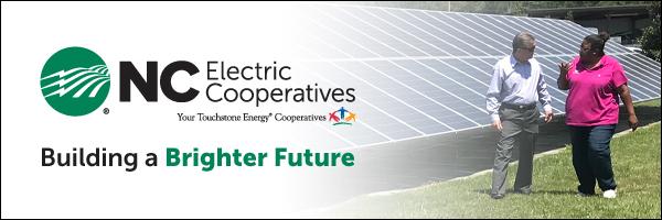 NCEMC Banner Ad Man and woman walking near solar panels